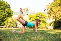 Giovane donna di sport che fa gli esercizi durante l'addestramento fuori nel parco della città All'aperto corrente di modello di  Fotografie Stock