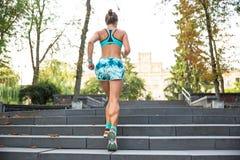 Giovane donna di sport che fa gli esercizi durante l'addestramento fuori nel parco della città All'aperto corrente di modello di  Fotografia Stock Libera da Diritti