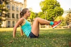 Giovane donna di sport che fa gli esercizi durante l'addestramento fuori nel parco della città All'aperto corrente di modello di  Immagini Stock