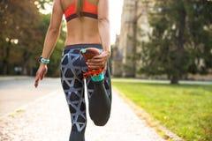 Giovane donna di sport che fa gli esercizi durante l'addestramento fuori nel parco della città All'aperto corrente di modello di  Immagine Stock