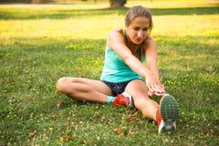 Giovane donna di sport che fa gli esercizi durante l'addestramento fuori nel parco della città All'aperto corrente di modello di  Immagine Stock Libera da Diritti