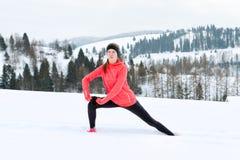 Giovane donna di sport che fa gli esercizi durante l'esterno di addestramento di inverno in montagne di inverno che indossano i g immagine stock libera da diritti