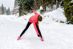 Giovane donna di sport che fa gli esercizi durante l'esterno di addestramento di inverno in montagne di inverno che indossano i g fotografia stock libera da diritti