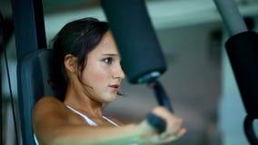 Giovane donna di sport che fa gli esercizi sulla macchina del Lat archivi video