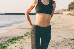 Giovane donna di sport che fa gli esercizi sulla spiaggia immagini stock libere da diritti