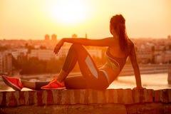 Giovane donna di sport che gode nel tramonto dopo un allenamento duro Fotografia Stock Libera da Diritti