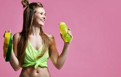 Giovane donna di sport con acqua di bottiglia bevente e la banda d'allungamento di gomma verde e gialla immagine stock