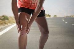 Giovane donna di sport con le forti gambe atletiche che tengono ginocchio con le mani nella lesione di sofferenza del legamento d fotografie stock
