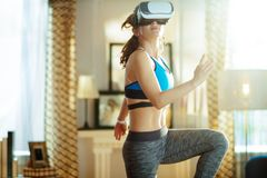 Giovane donna di sport in salone moderno nell'allenamento di vetro di VR fotografie stock libere da diritti