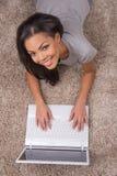 Giovane donna di vista superiore che si trova sulla pavimentazione del tappeto fotografia stock libera da diritti