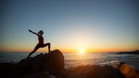 Giovane donna di yoga della siluetta che fa gli esercizi di forma fisica sulla spiaggia del mare fotografie stock