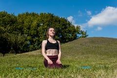 giovane donna di yogini che si siede sulle ginocchia immagine stock libera da diritti