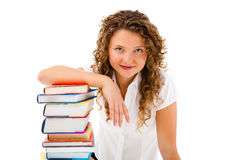 Giovane donna dietro il mucchio dei libri isolati su bianco Immagini Stock