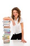 Giovane donna dietro il mucchio dei libri isolati su bianco Fotografie Stock Libere da Diritti
