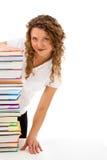 Giovane donna dietro il mucchio dei libri isolati su bianco Fotografia Stock