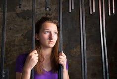 Giovane donna dietro le barre immagini stock