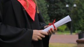 Giovane donna in diploma accademico della tenuta del vestito, godente della graduation archivi video
