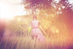 Giovane donna in dirndl che cammina da solo nel campo Immagini Stock