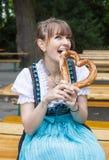 Giovane donna in dirndl con la ciambellina salata Fotografie Stock Libere da Diritti