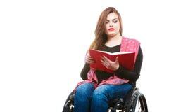 Giovane donna disabile in sedia a rotelle con il libro fotografie stock
