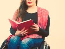 Giovane donna disabile in sedia a rotelle con il libro immagine stock