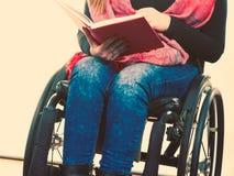 Giovane donna disabile in sedia a rotelle con il libro immagine stock libera da diritti