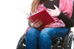 Giovane donna disabile in sedia a rotelle con il libro fotografia stock