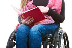 Giovane donna disabile in sedia a rotelle con il libro immagini stock libere da diritti