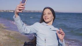 Giovane donna disabile in sedia a rotelle divertendosi sulla spiaggia di sabbia vicino al mare Fucilazione con il suoi telefono e video d archivio