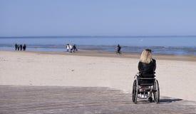 Giovane donna disabile sola sulla spiaggia Giorno di estate pieno di sole fotografia stock libera da diritti