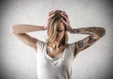 Giovane donna disperata con i tatuaggi Fotografia Stock
