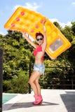 Giovane donna divertendosi con il materasso giallo immagini stock