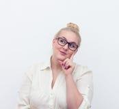 Giovane donna dubbiosa che pensa, sul bianco Fotografie Stock Libere da Diritti