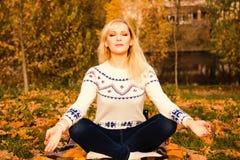 Giovane donna durante rilassamento e la meditazione in parco Fotografia Stock