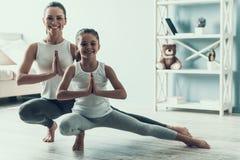 Giovane donna e bambina che fanno posa di yoga fotografie stock libere da diritti