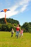 Giovane donna e bambini che pilotano un cervo volante Fotografie Stock