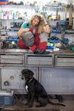 Giovane donna e cane in un negozio del meccanico Immagini Stock