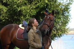 Giovane donna e cavallo marrone insieme nella foresta Fotografie Stock