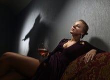 Giovane donna e l'ombra del ` s del colpevole sulla parete fotografie stock
