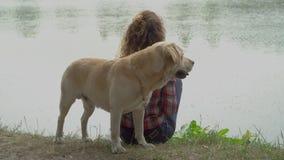 Giovane donna e labrador vicino al fiume stock footage