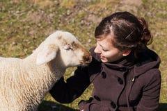 Giovane donna e piccolo agnello che se esaminano Fotografia Stock