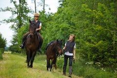 Giovane donna e ragazza che montano i loro cavalli Fotografie Stock Libere da Diritti