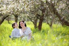 Giovane donna ed il suo bambino che hanno resto nel giardino della mela di primavera immagine stock libera da diritti