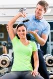 Giovane donna ed istruttore all'esercizio in palestra immagine stock