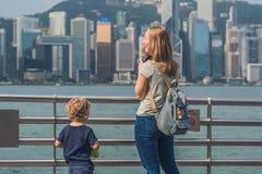 Giovane donna ed suo figlio che prendono le foto del porto di Victoria in Hong Kong, Cina fotografia stock libera da diritti