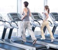 Giovane donna ed uomo all'esercitazione di ginnastica. Funzionare Immagine Stock Libera da Diritti