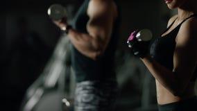 Giovane donna ed uomo che fanno un allenamento di forma fisica con le teste di legno video d archivio
