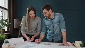 Giovane donna ed uomo come architetti che lavorano con i modelli, il computer portatile ed i modelli della casa nell'ufficio stock footage