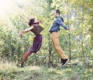 Giovane donna ed uomo in vestiti luminosi che saltano per incontrarsi Fotografia Stock Libera da Diritti