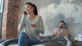 Giovane donna egoista che parla sulla cote e che trascura marito malato archivi video